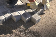 stock-footage-mason-worker-making-sidewalk-pavement-with-stone-brinks